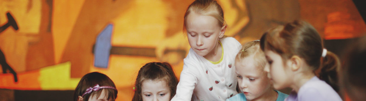 Zdjęcie. Grupa dzieci w skupieniu pracuje nad zadaniem. W tle fragment ściennego obrazu Fangora w Muzeum Warszawy.