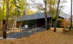 wejście domuzeum, schody, ziemia pokryta liśćmi, wokół las