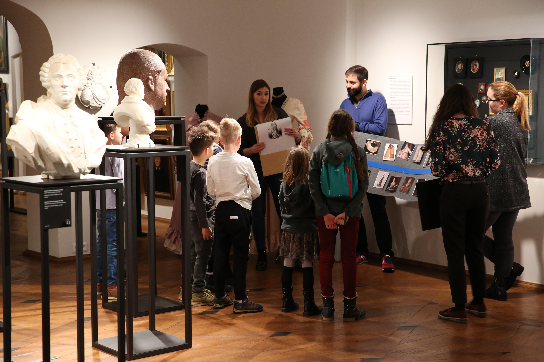 Edukatorka Muzeum Warszawy przedstawia planszę grupie dzieci zwiedzających wystawę główną.