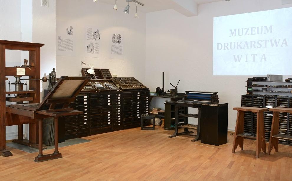 Wnętrze Muzeum Drukarstwa. Zabytkowa, drewniana prasa drukarska, szafy zecerskie zkasztami (szufladkami) wypełnionymi czcionkami, prasa litograficzna.