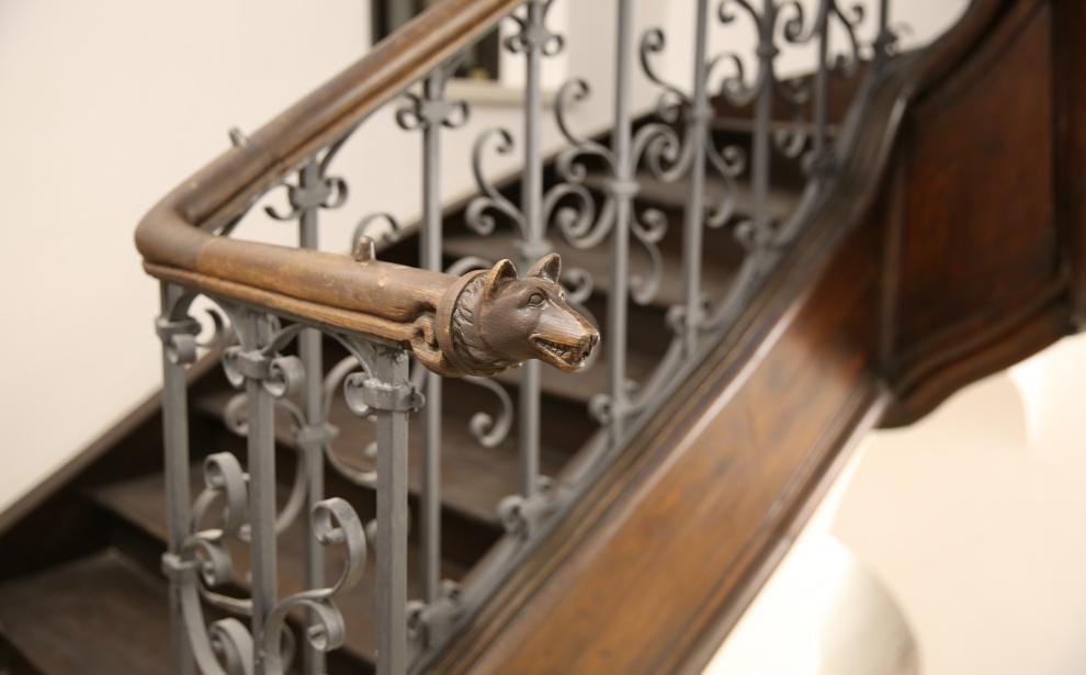 Drewniane schody zmetalową, fantazyjnie kutą balustradą. Drewniana poręcz zakończona ręcznie rzeźbioną głową wilka.