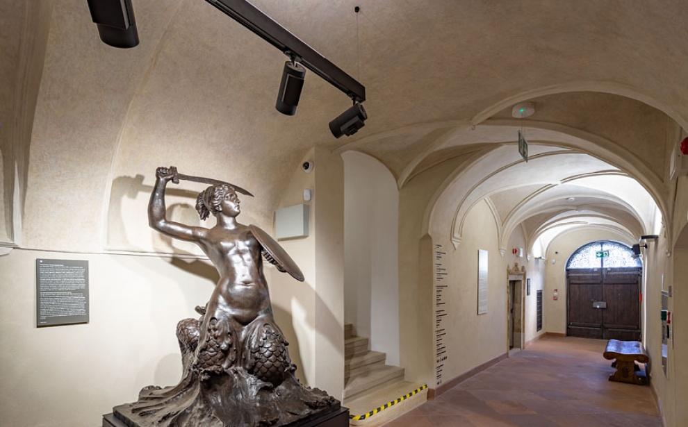 Długi, ciemny korytarz Muzeum Warszawy. Sklepiony, biały sufit. Polewej stronie Pomnik Syreny mocno oświetlony punktowym światłem.