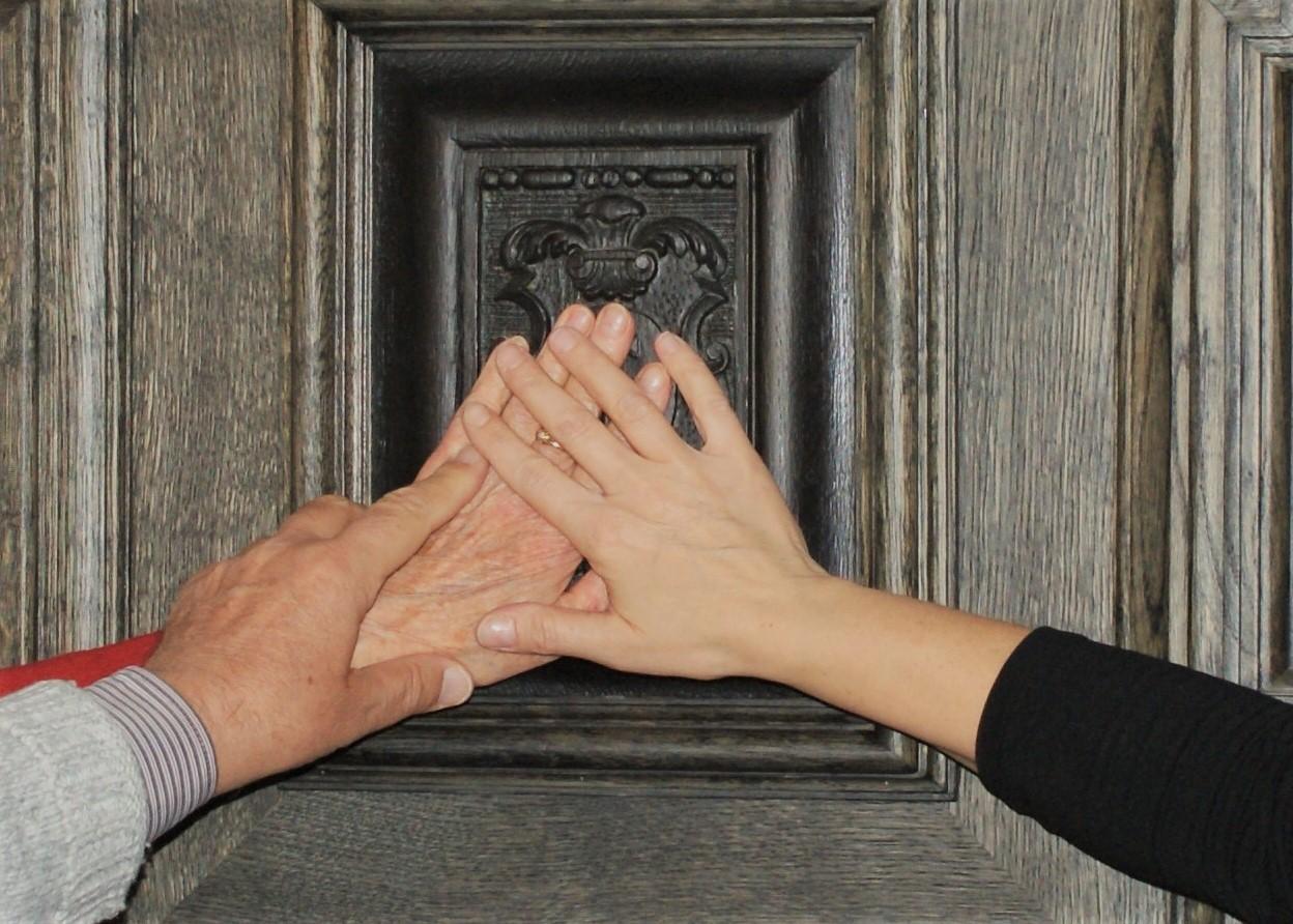 Fragment płyciny drzwi. Trzy dłonie dotykające płaskorzeźby napłycinie.