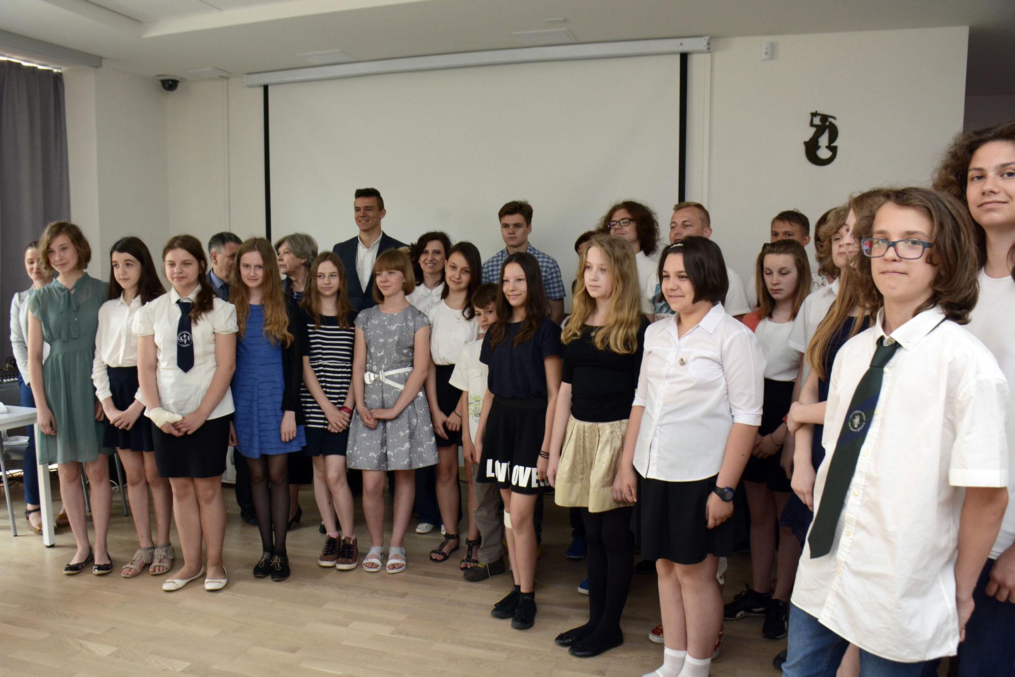Zgromadzeni w sali laureaci konkursu pozują do grupowego zdjęcia.