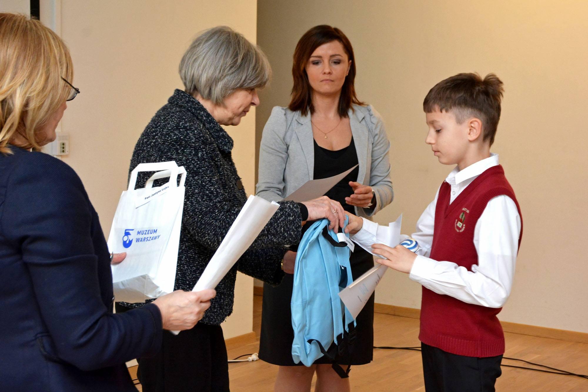 Dyrektor muzeum Ewa Nekanda Trepka wręcza nagrodę, niebieski plecak, laureatowi konkursu