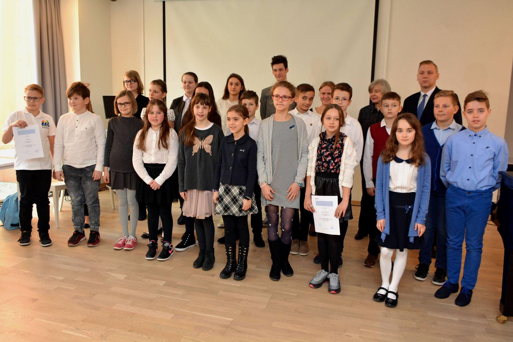 W zamkniętej sali grupa dzieci, laureatów konkursu, pozuje do zdjęcia.