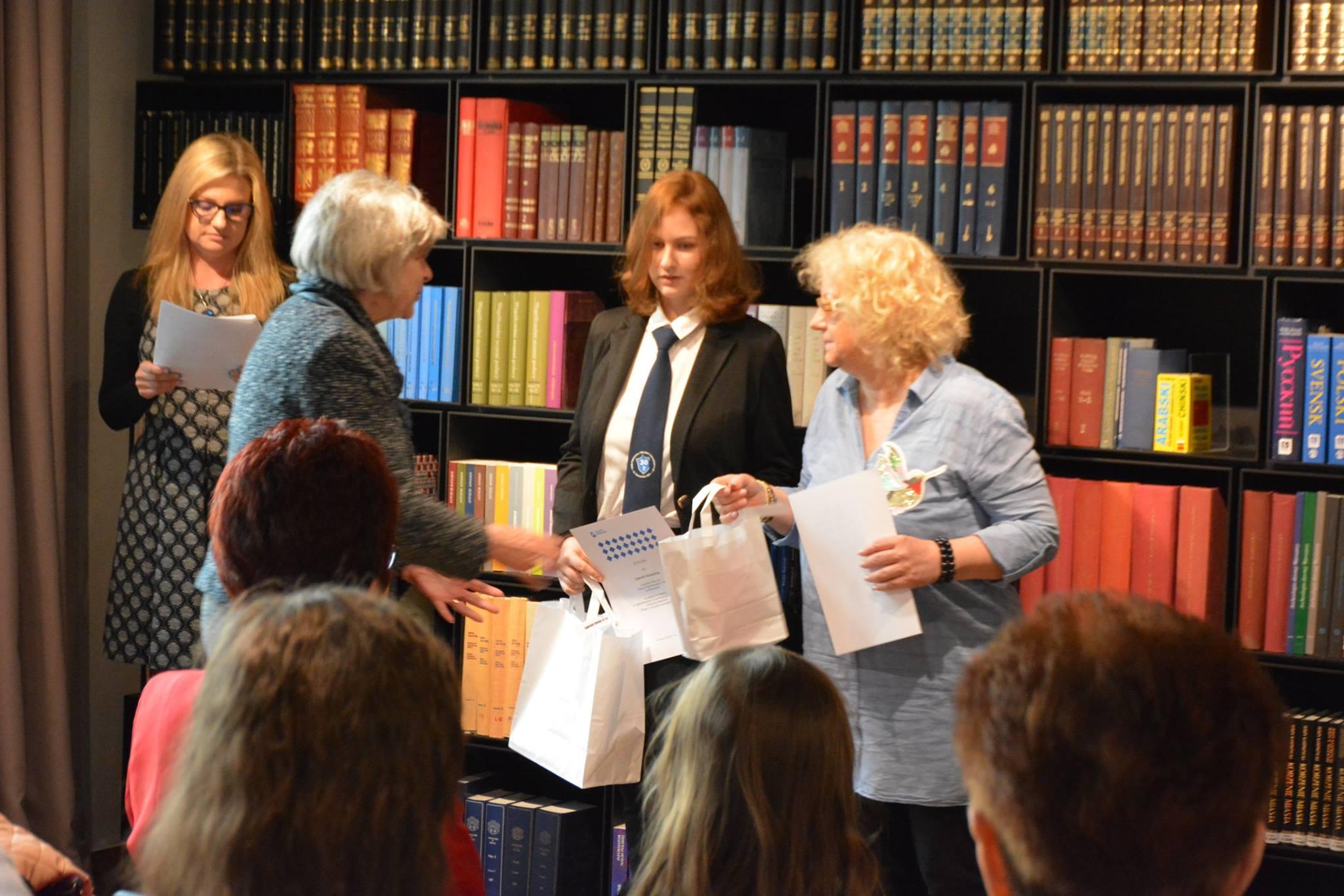W bibliotece muzealnej dyrektor Ewa Nekanda Trepka wręcza nagrodę laureatce konkursu oraz jej opiekunowi.