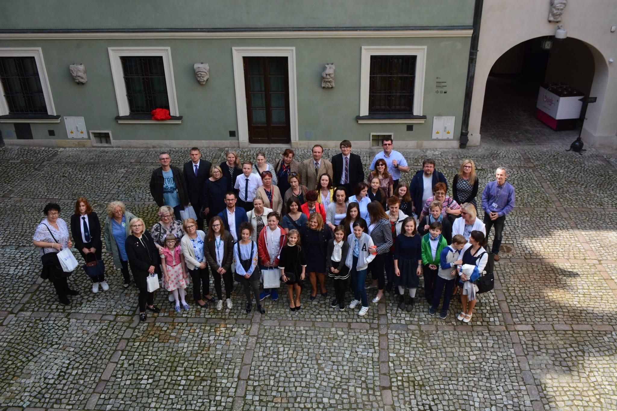 Zdjęcie zrobione z góry, na zewnątrz na tle kamienic muzealnych stoi grupa laureatów z nagrodami.