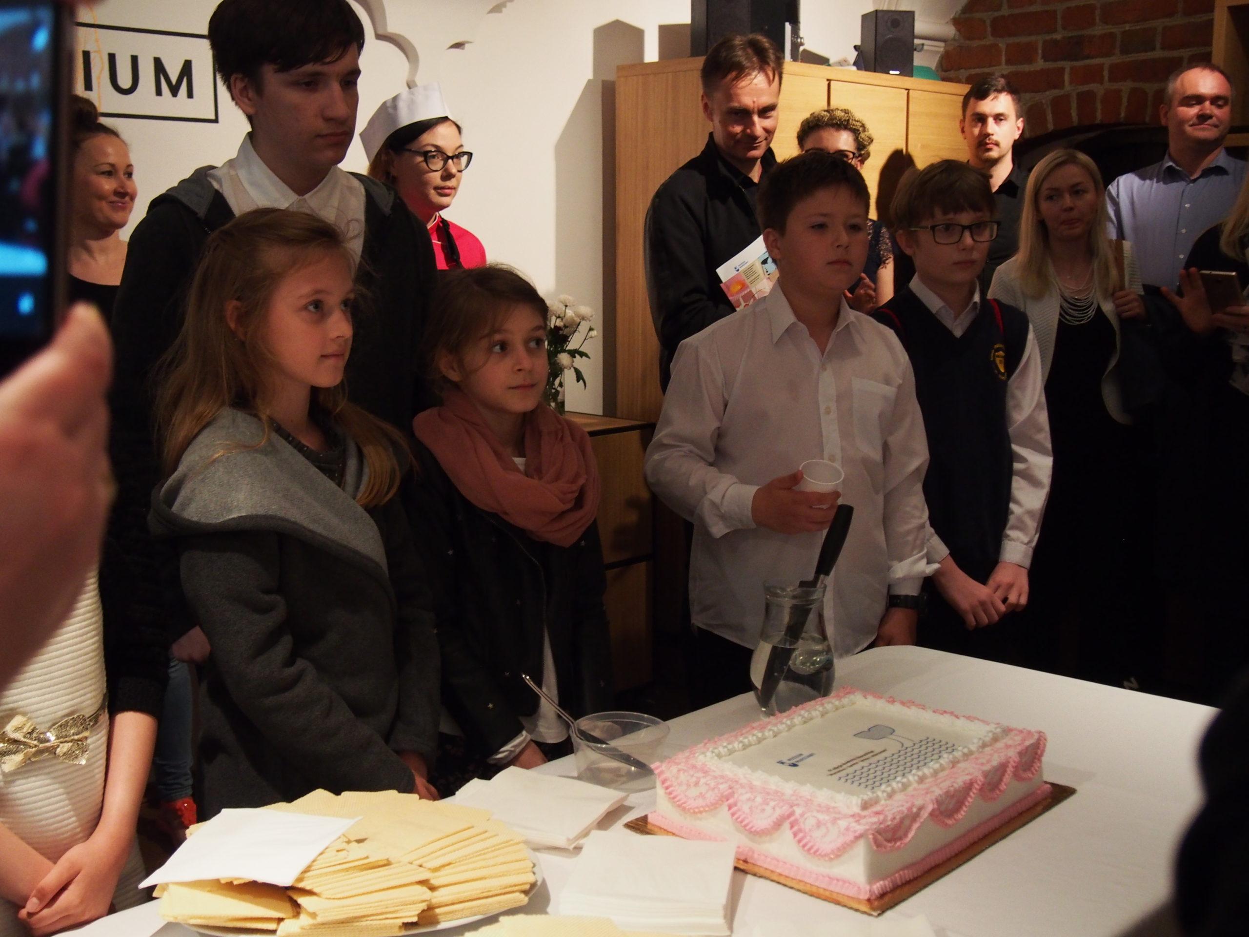 Na pierwszym planie na stole leży planie prostokątny tort. Wokół stołu grupka dzieci- laureatów konkursu.