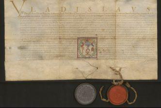 Pożółkły rękopis z napisem Vlaidslaus na górze, pod spodem dwie okrągłe pieczęcie z laki zamocowane na sznurkach.