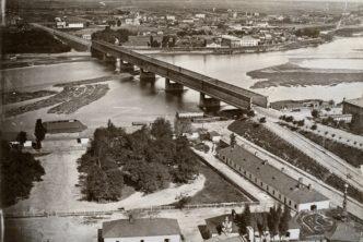 Czarno białe zdjęcie Warszawy z lotu ptaka. Widoczny fragment Wisły i nieistniejącego mostu Kierbedzia. mostu