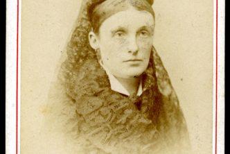 Dawna fotografia kobiety w średnim wieku, z upiętymi w kok włosami i szalem wokół szyji