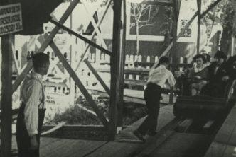 Czarno białe zdjęcie. Ludzie siedzący w kolejce górskiej w wesołym miasteczku.