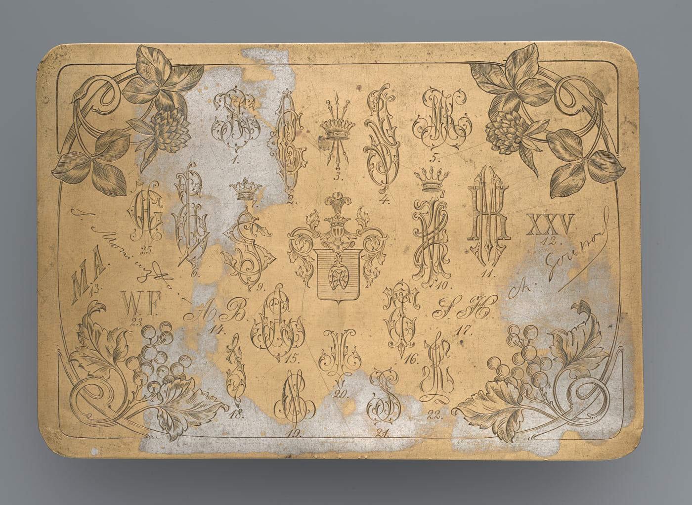 blaszka wkolorze złotym zwyrytymi ozdobnymi kwiatami, literami iherbami