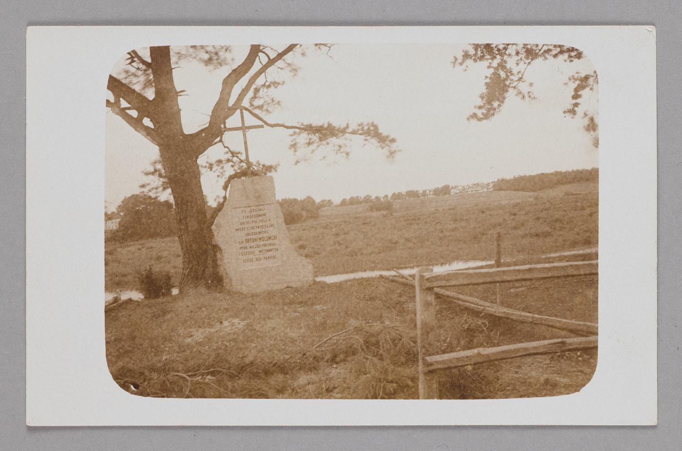 Zdjęcie. Nazewnątrz polewej stronie drzewo, obok kamienny pomnik zinskrypcją.