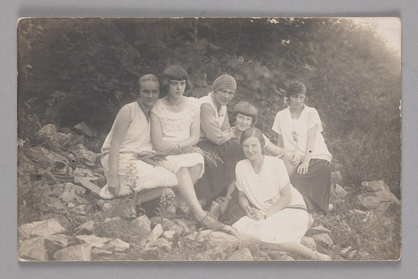 Zdjęcie grupy sześciu kobiet wbiałych sukienkach ikoszulach, siedzących nazewnątrz natle zieleni.