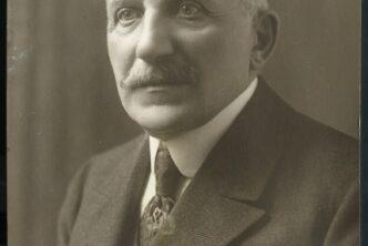 Zdjęcie Oskara Hartwiga, starszy mężczyzna, w garniturze, z wąsem, na szarym tle