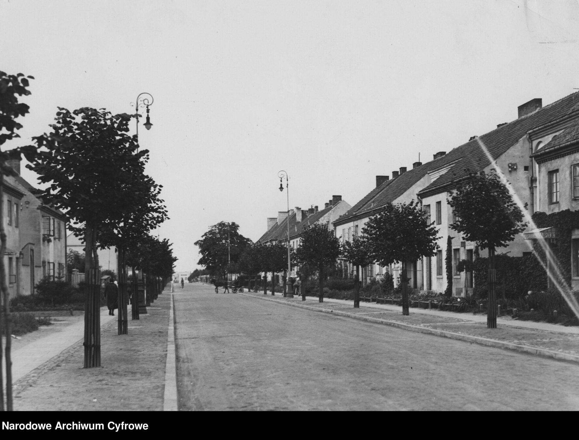 Czarno białe zdjęcie archiwalne. Pusta ulica, wzdłuż niej drzewa ilatarnie orazchodnik dla pieszych. Przy chodniku poobu stronach niska zabudowa jednorodzinna.