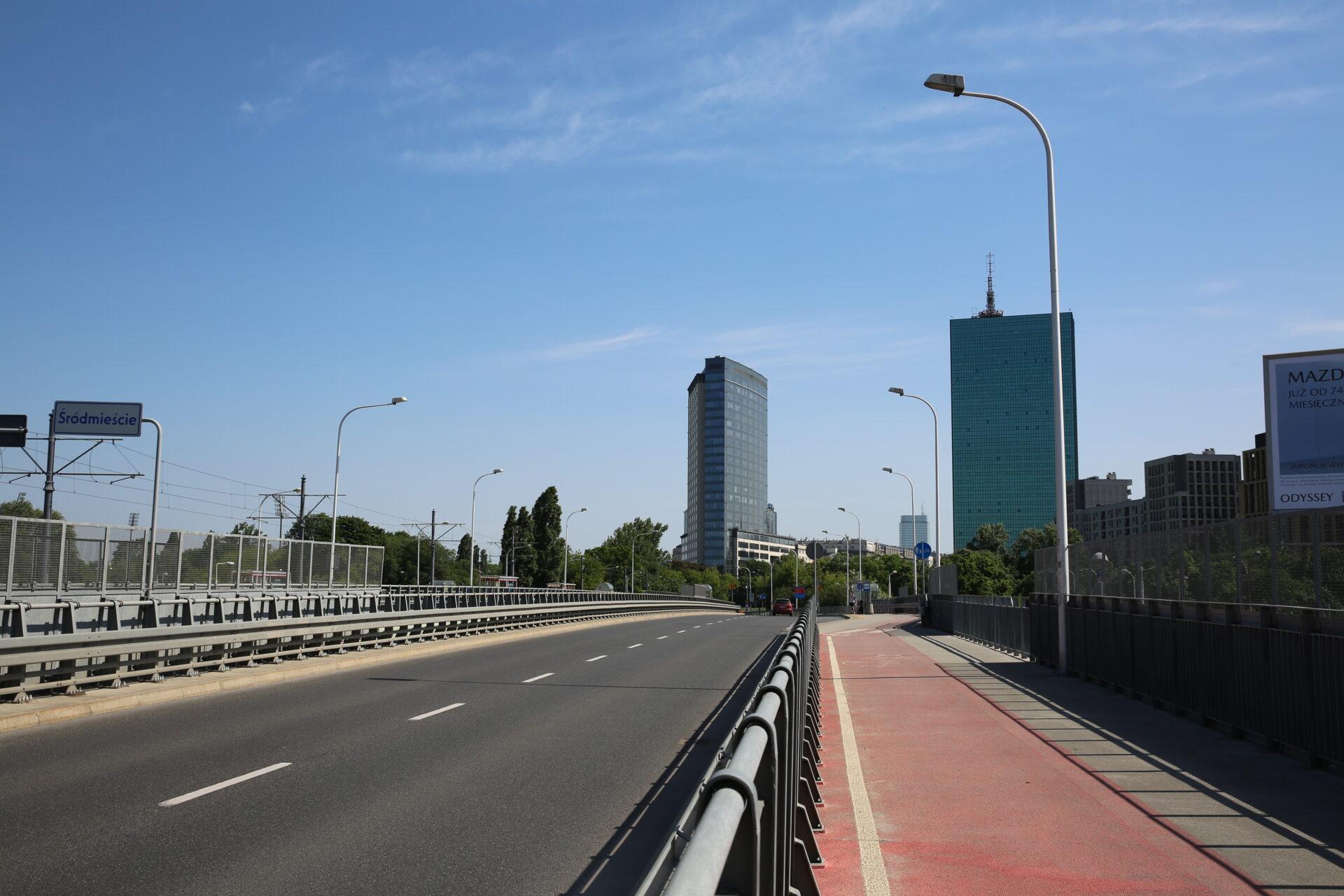 Zdjęcie współczesne. Droga nawiadukcie. Wtle dwa wysokie, szklane budynki.