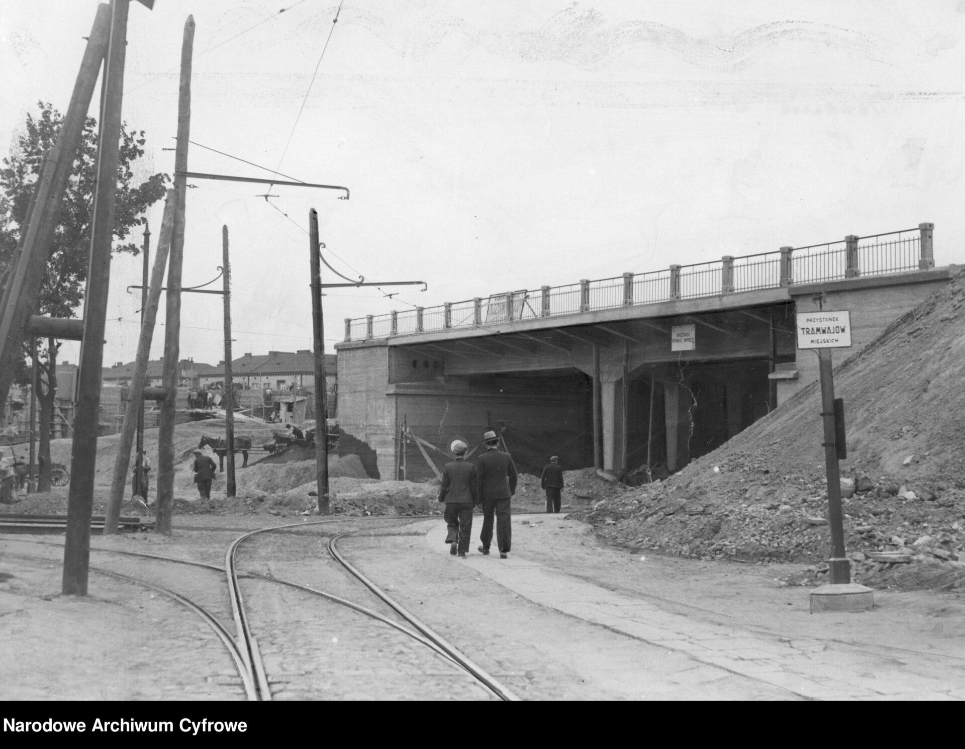 Czarno białe zdjęcie. Wiadukt wbudowie, poprawej stronie kupa gruzu. Wstronę wiaduktu kroczy kilku mężczyzn.