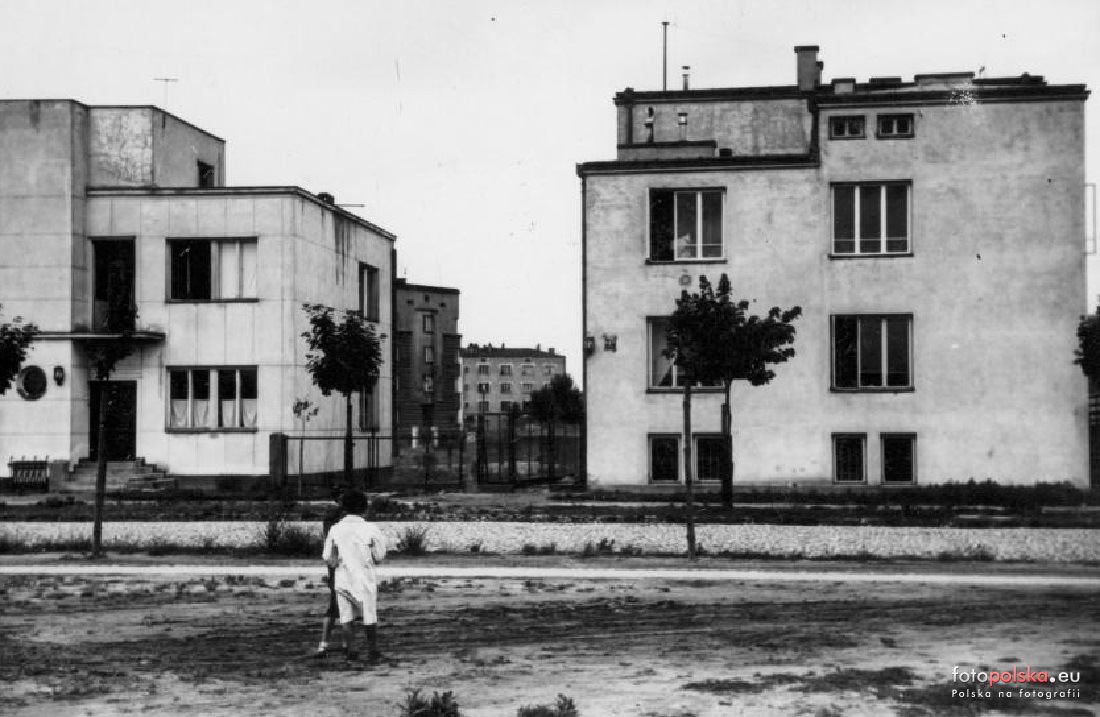 Czarno białe zdjęcie. Dwa dwupiętrowe sześcienne budynki. Przednimi dwie osoby.