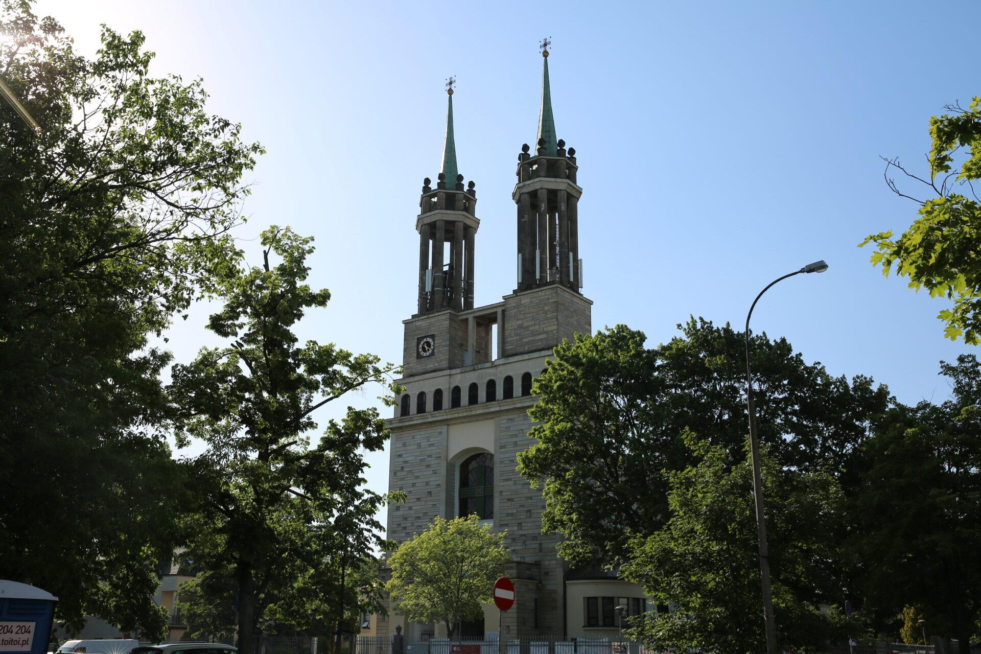 Dwie, ażurowe wieże kościoła pośród drzew.