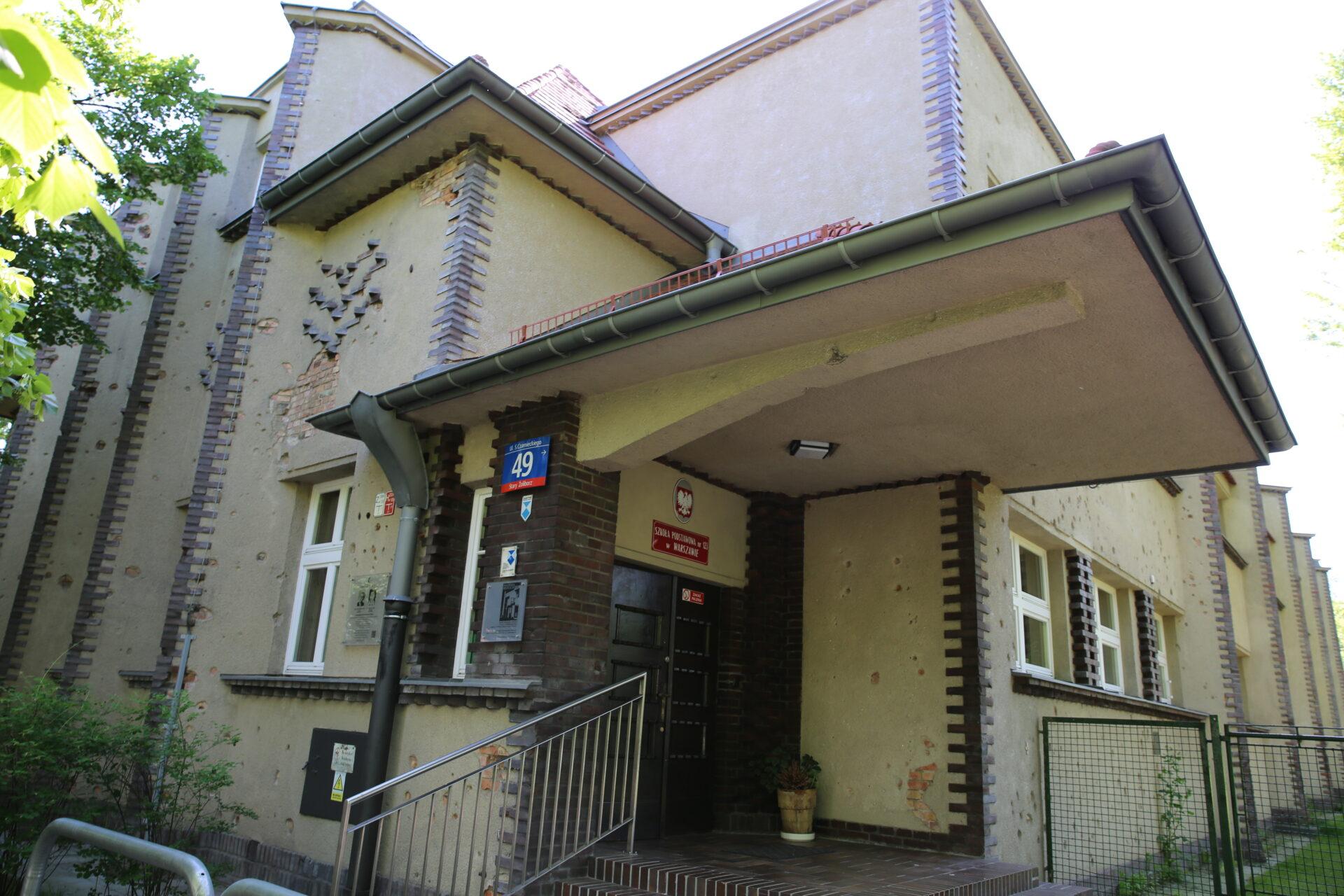 Zdjęcie kolorowe, współczesne. Wejście dobudynku szkolnego.