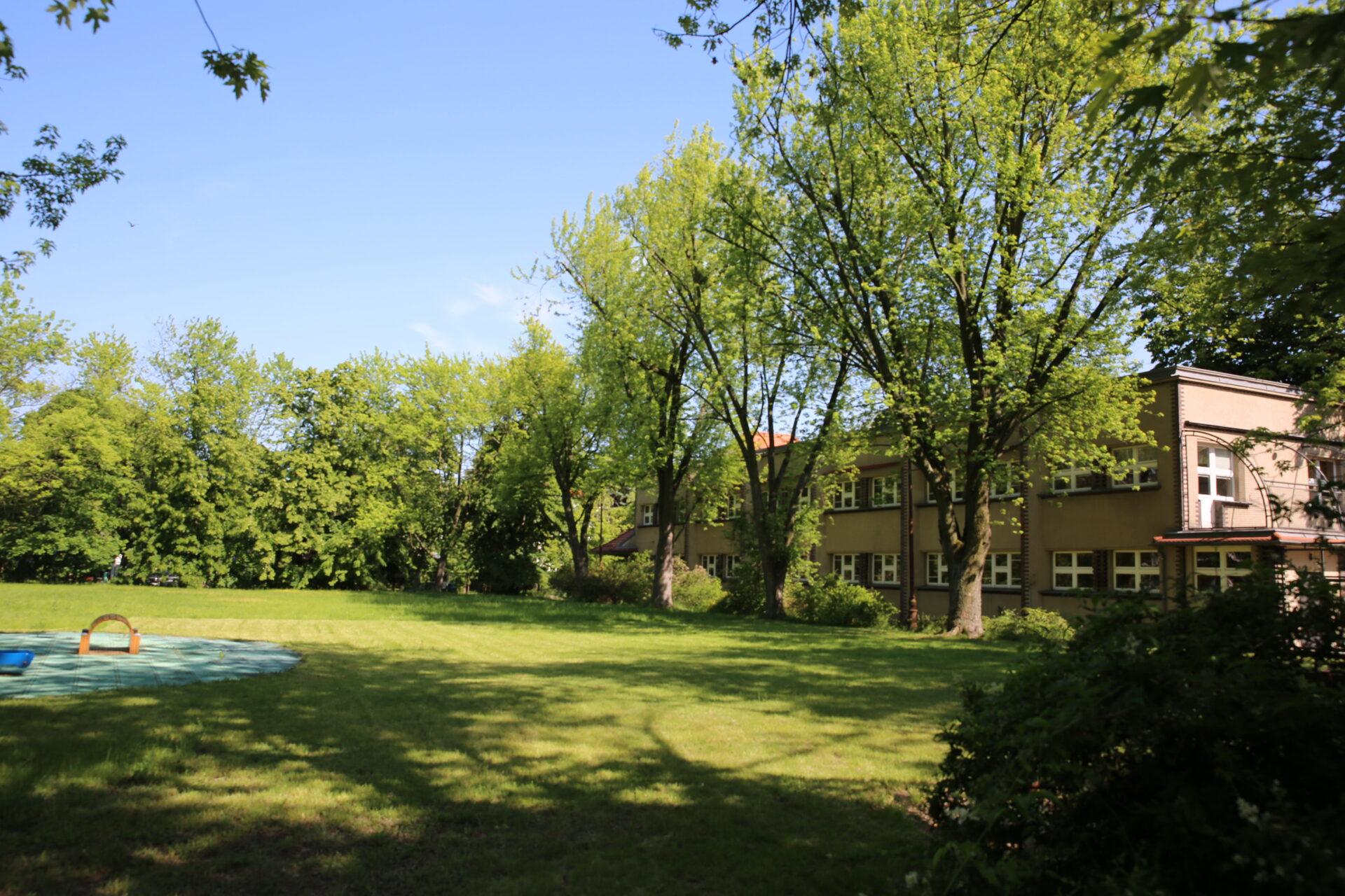 Zdjęcie kolorowe, współczesne. Plac porośnięty trawą, wokół krzaki idrzewa. Poprawej stronie placu dwukondygnacyjny budynek.