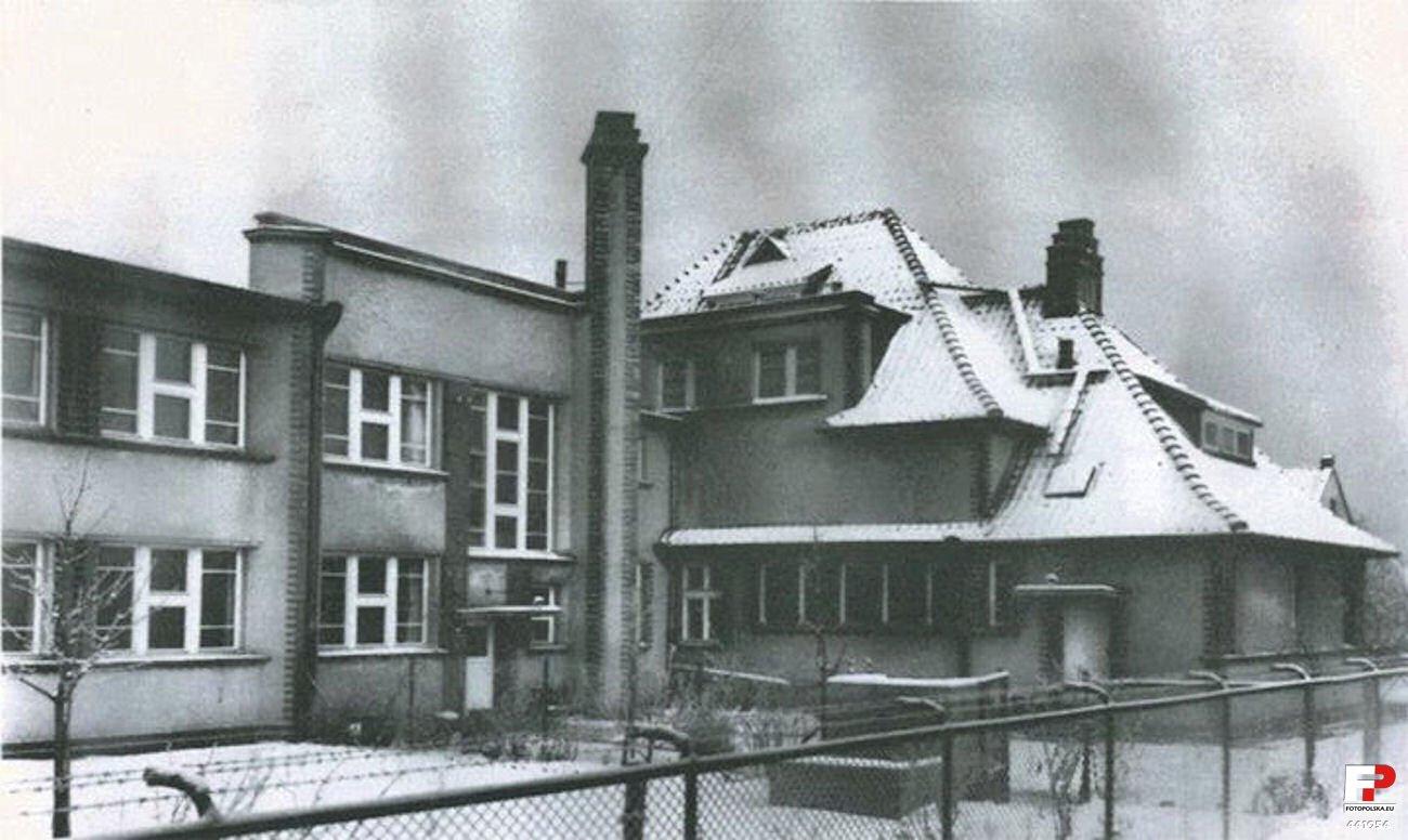 Czarno białe zdjęcie archiwalne. Budynek szkolny zasiatkowym płotem. Spadzisty dach budynku przykryty śniegiem.