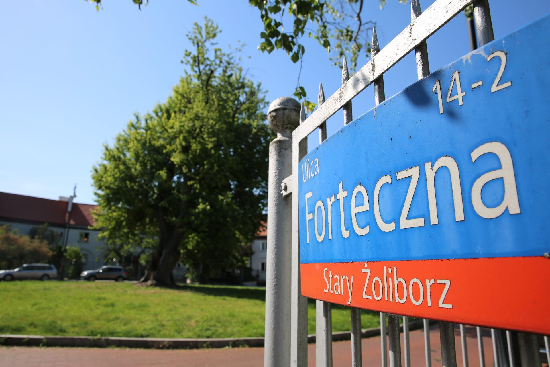Zdjęcie kolorowe, współczesne. Fragment bramy ztabliczką znazwą: Ulica Forteczna 14-2, Stary Żoliborz. W tle zabramą zielone, wysokie drzewo ifragmentu budynku.