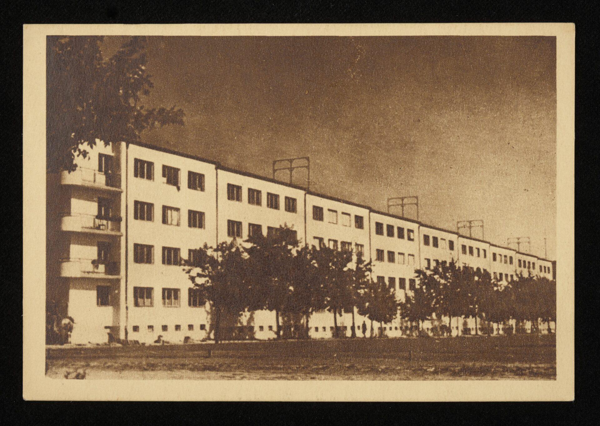 Czarno białe zdjęcie archiwalne. Jasny blok mieszkalny zczterema kondygnacjami. Przednim zasadzone drzewa.