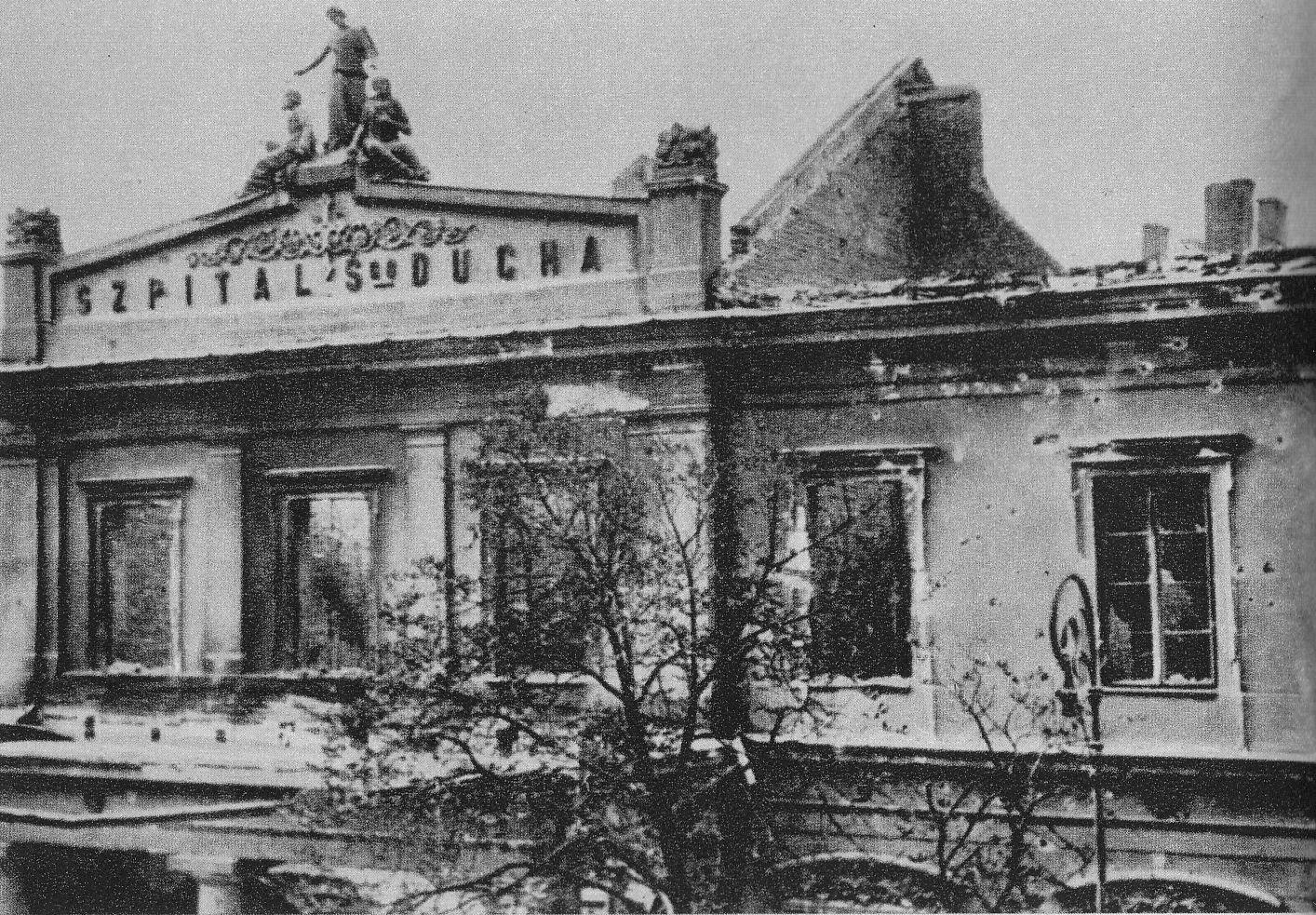 Czarno białe zdjęcie archiwalne. Fragment fasady budynku. Ciąg okien inapis Szpital świętego ducha.