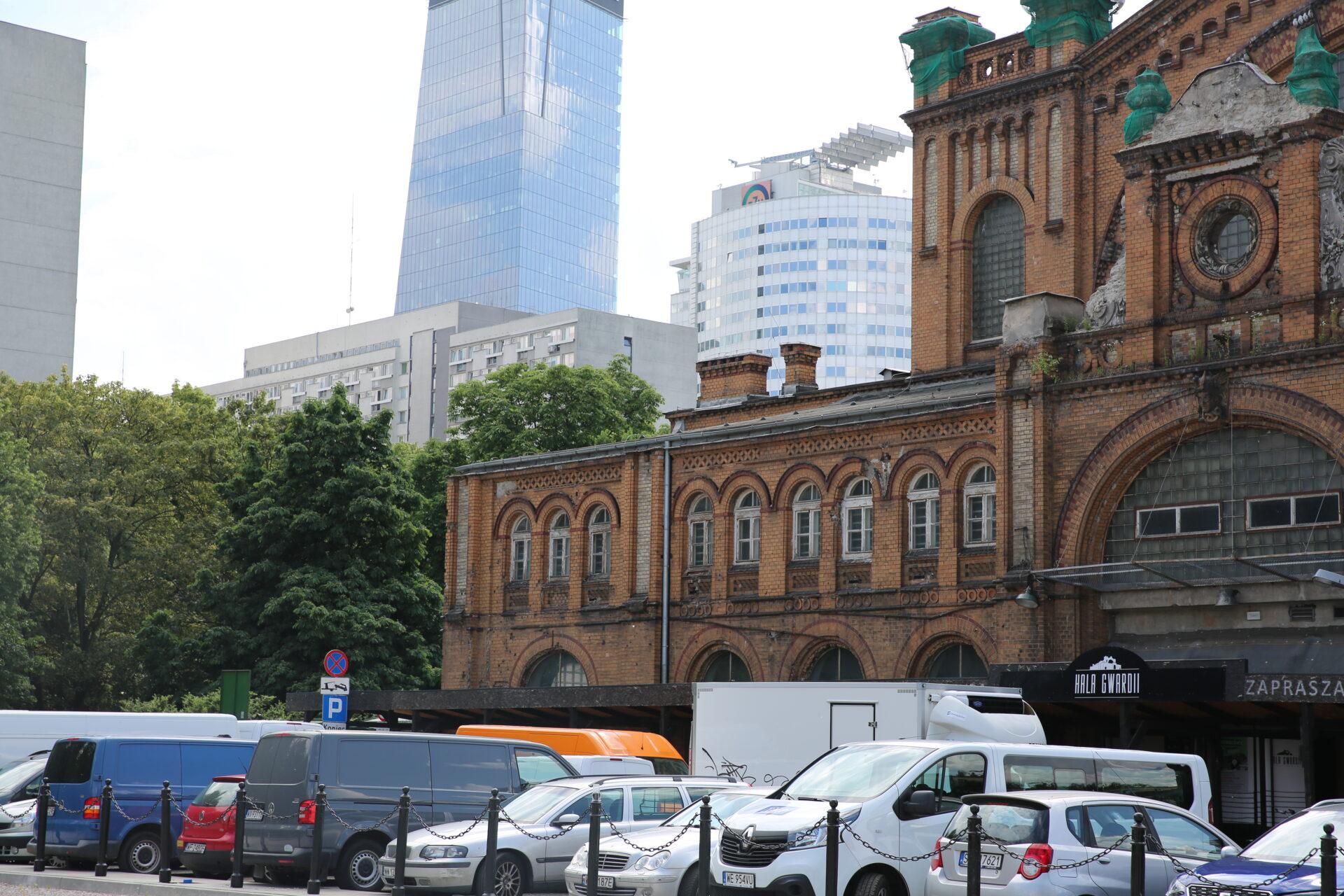 Zdjęcie współczesne. Napierwszym planie zaparkowane samochody. Wtle ceglany budynek Hali Gwardii, zanim nowoczesne, szklane budynki.