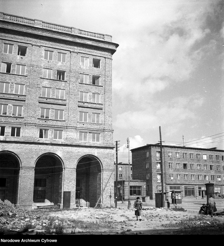 Zdjęcie archiwalne, czarno białe. Dwa wysokie ceglane budynki wczasie budowy. Obok spacerujący ludzie.