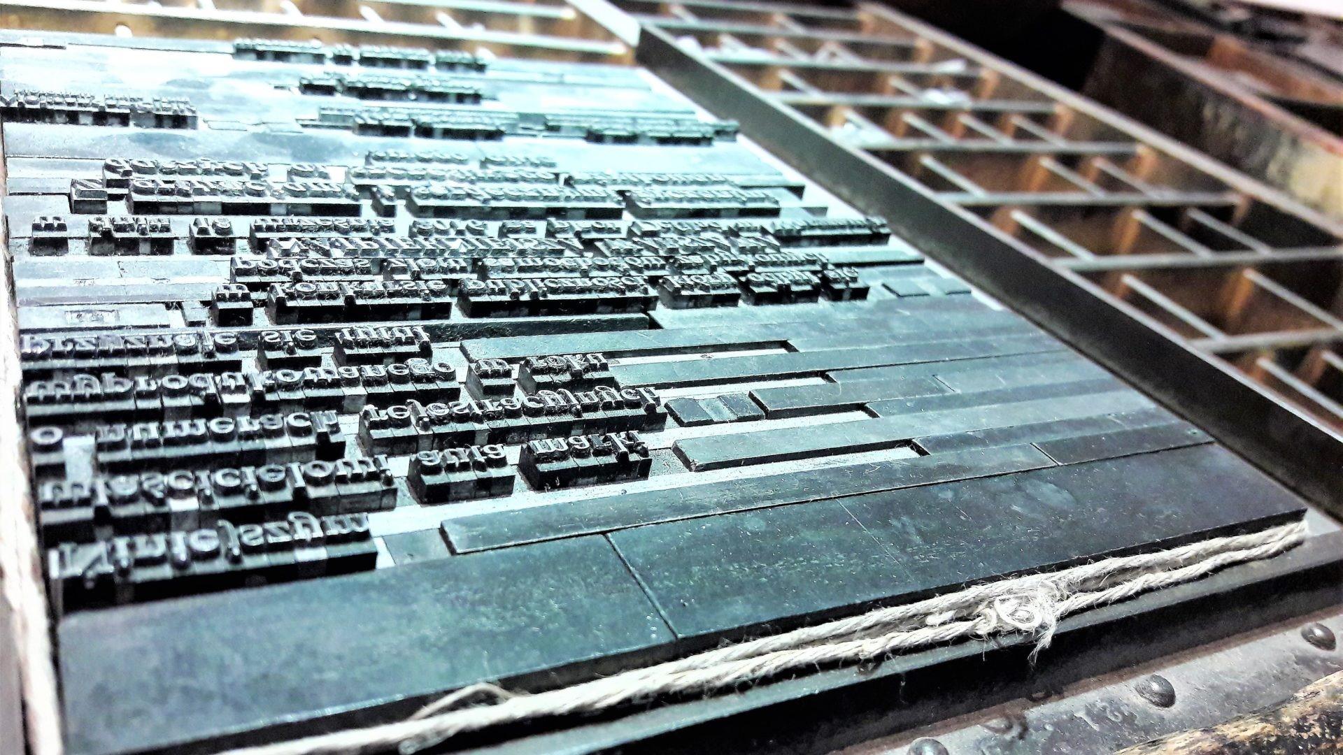 Skład drukarski ułożony nadrewnianej szufloramie, związany sznurkiem. Skład przygotowany dodruku. Fot.Muzeum Drukarstwa
