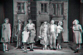 Zdjęcie za spektaklu Róża na Skaryszewskiej. Aktorzy na scenie. Za nimi dekoracje przedstawiające ściany kamienicy.