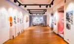Zdjęcie przestrzeni wystawowej. Podłuzne, jasne pomieszczenie. Naścianach powieszone kolorowe zdjęcia.