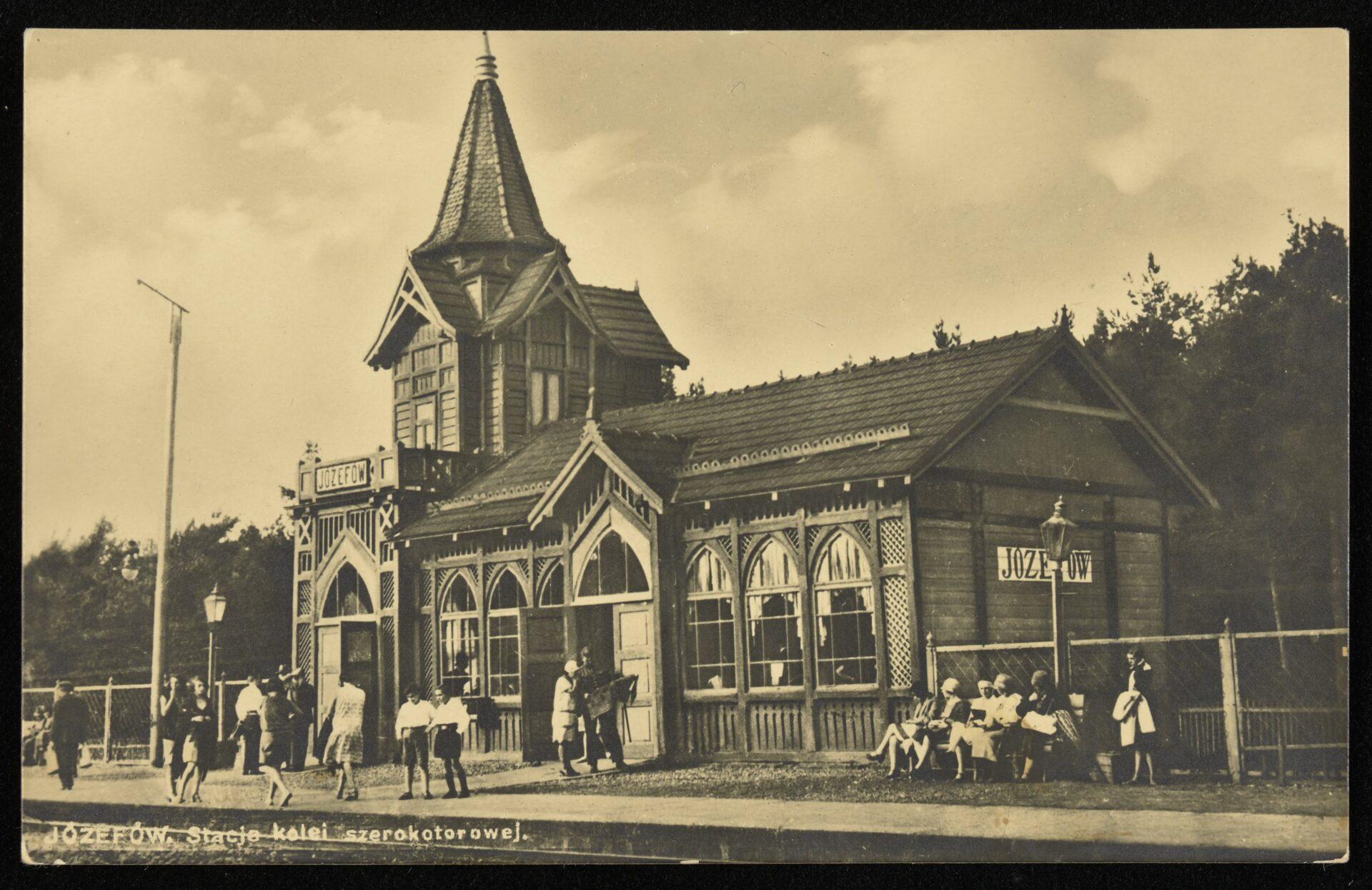 Zdjęcie archiwalne, czarno-białe. Drewniany budynek stacji kolejowej wJózefowie. Przednim zgromadzeni ludzie.