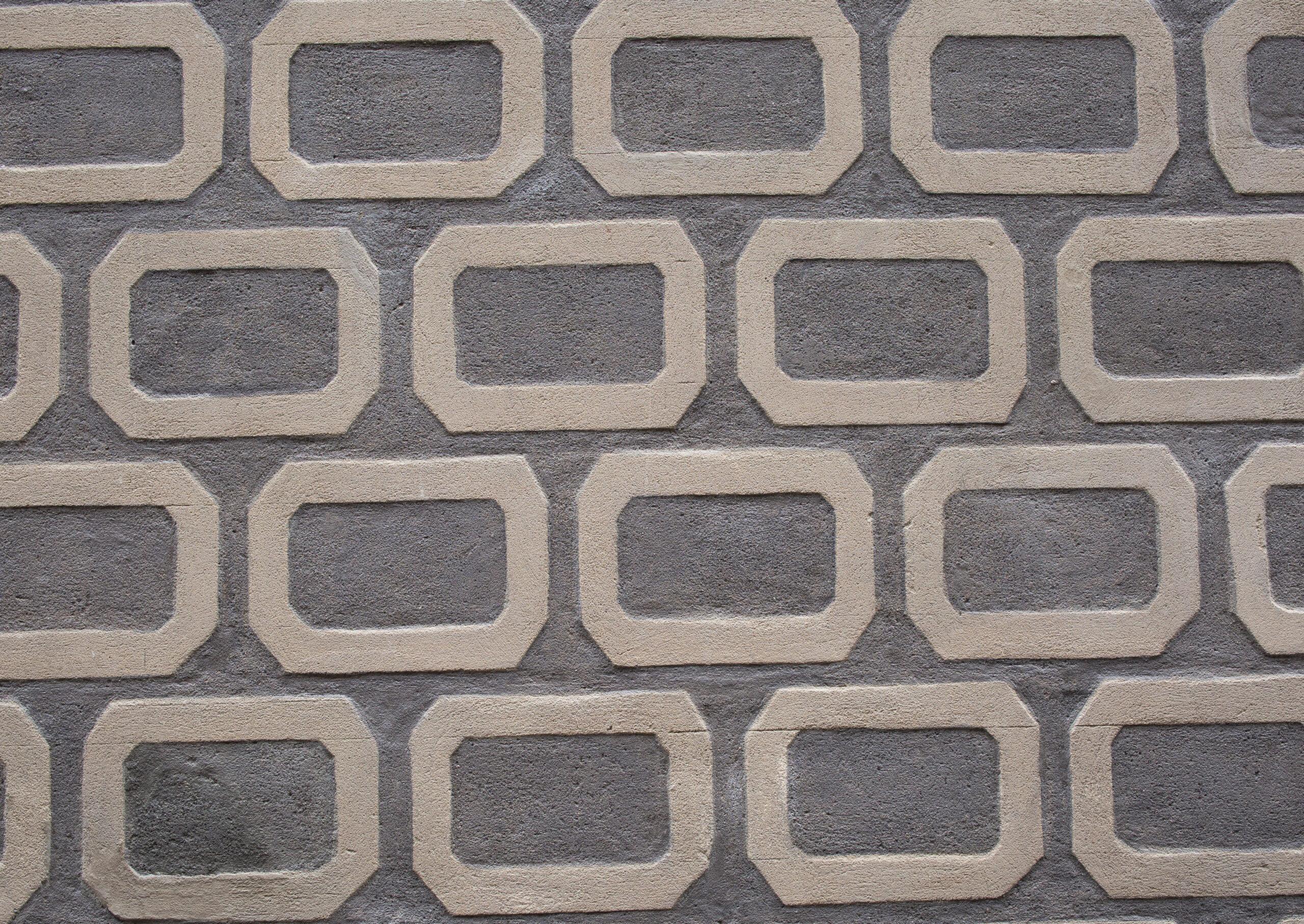 Fotografia fragmentu fasady. Sgraffito ogeometrycznym wzorze. Jasne wypukłe prostokątny ześciętymi narożami natle ciemnoszarej ściany.