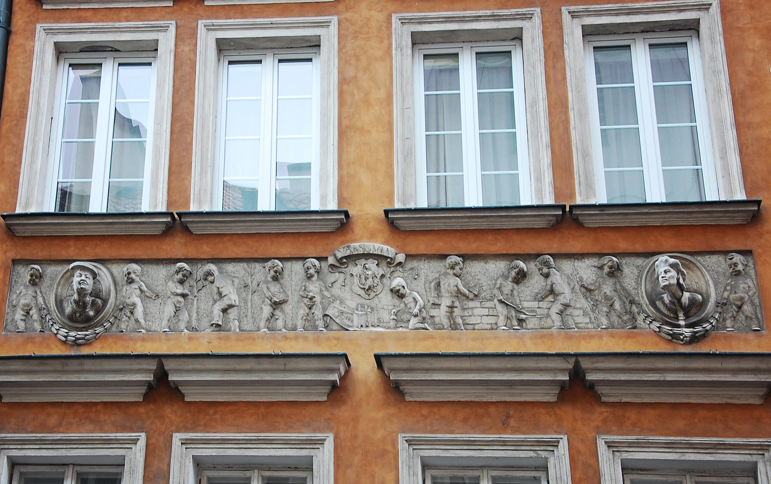 Zdjęcie fragmentu fasady kamienicy. Dwa rzędy okien, między nimi płaskorzeźbiony fryz zpracującymi puttami.