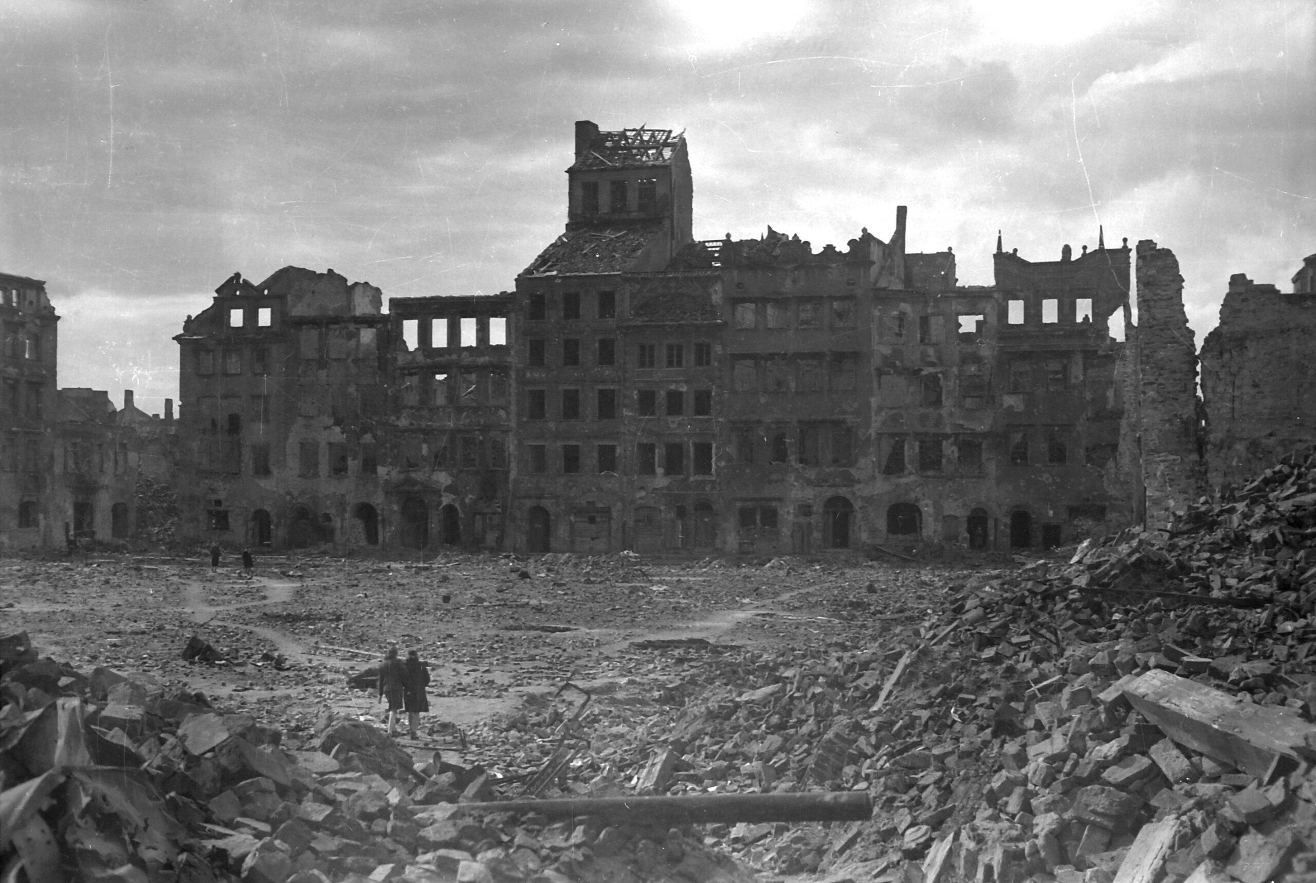 Czarno-biała fotografia zniszczonych kamienic przy Rynku Starego Miasta. Narynku mnóstwo gruzu iruin. Pomiędzy ruinami idą dwie skulone postacie.