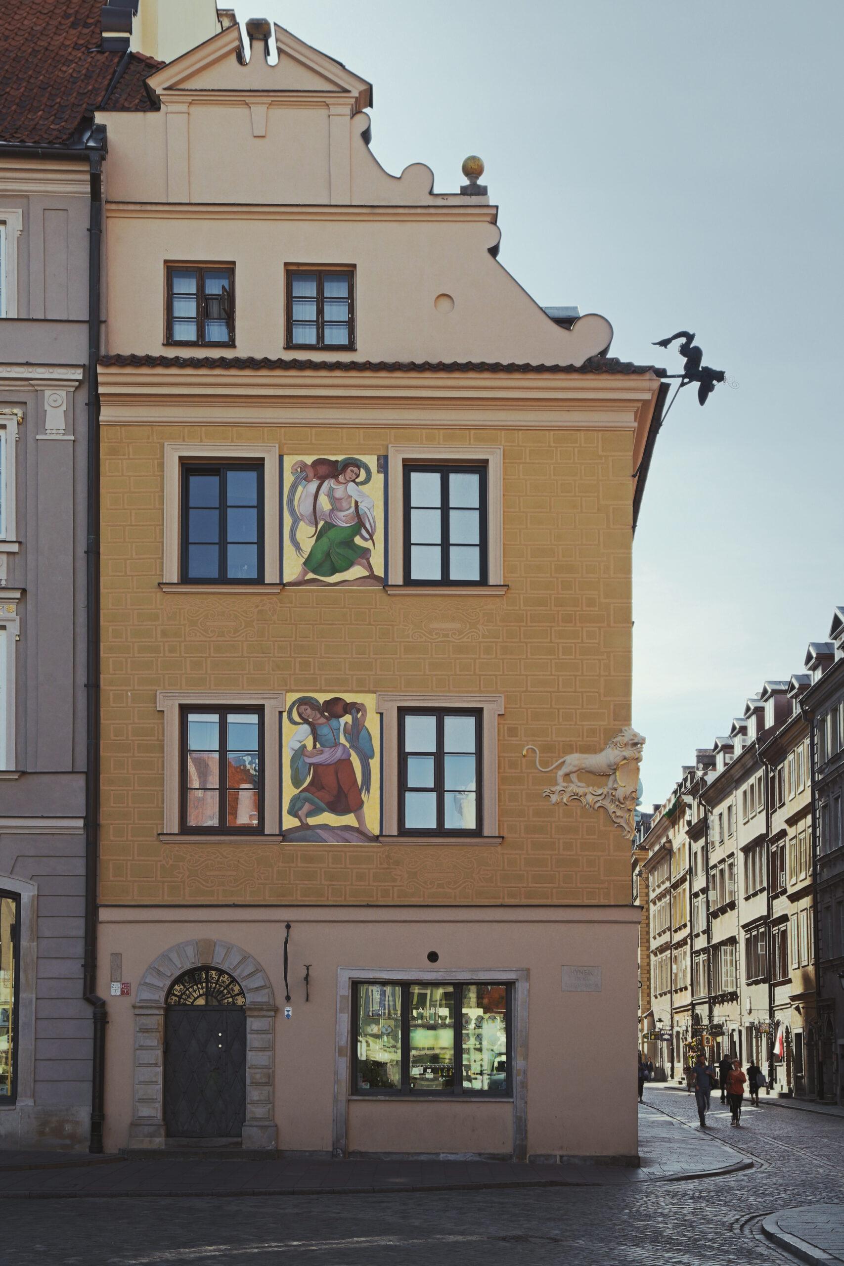 Fotografia fasady kamienicy zdwoma wielobarwnymi malowidłami przedstawiającymi kobiety.