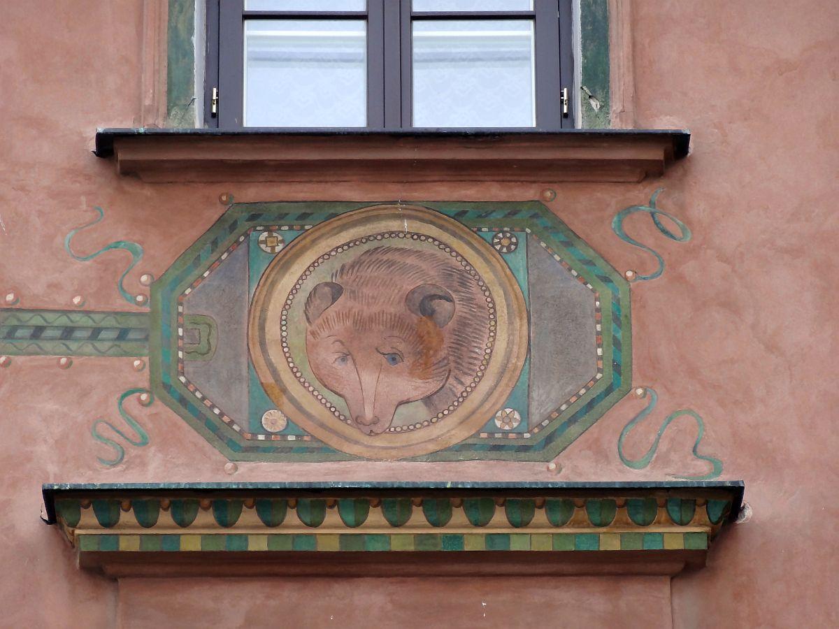 Fotografia fragmentu fasady. Między oknami polichromia. Głowa niedźwiedzia wozdobnej ramie.