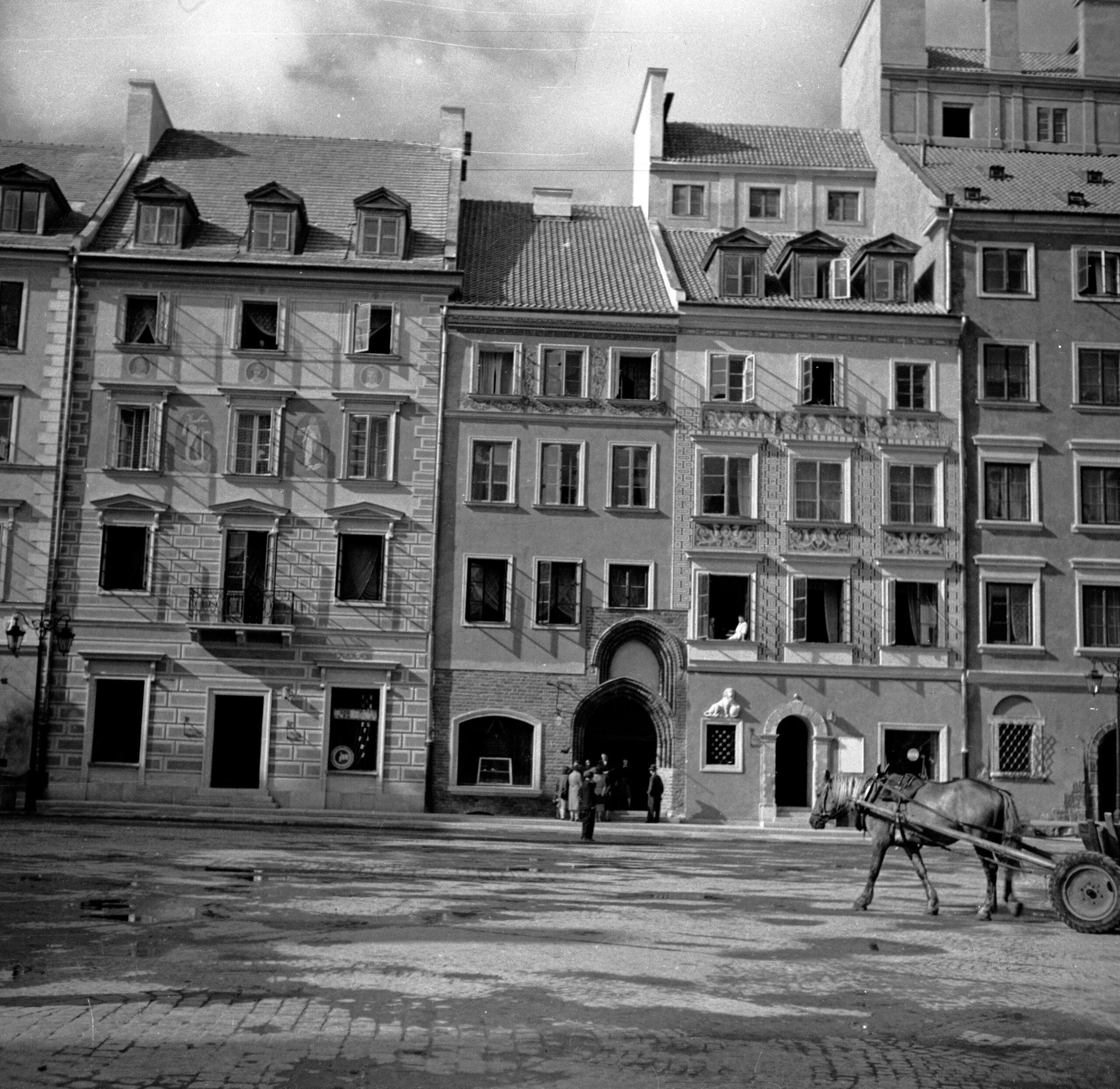 Czarno-biała fotografia fasad trzech zciągu kamienic. Środkowa zpodwójnym portalem gotyckim.