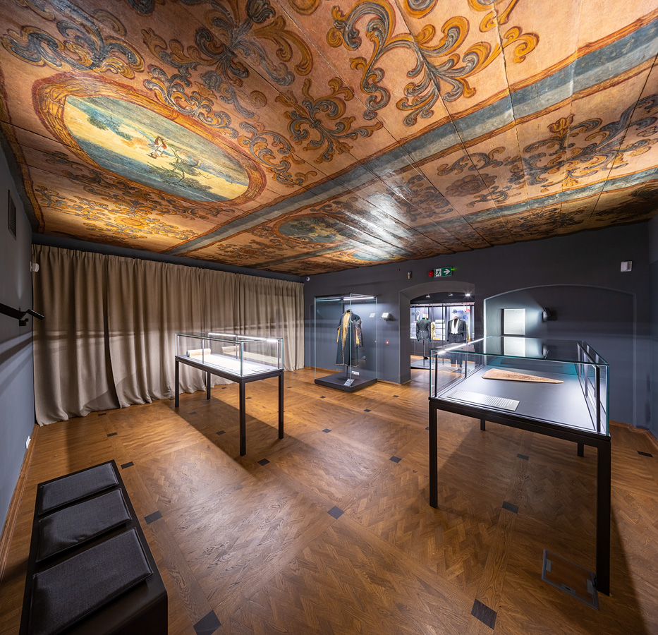 Fotografia wnętrza gabinetu wystawowego. Okna zasłonięte kotarami, drewniany sufit ozdobiony kolorowymi polichromiami. Trzy szklane gabloty zeksponatami.