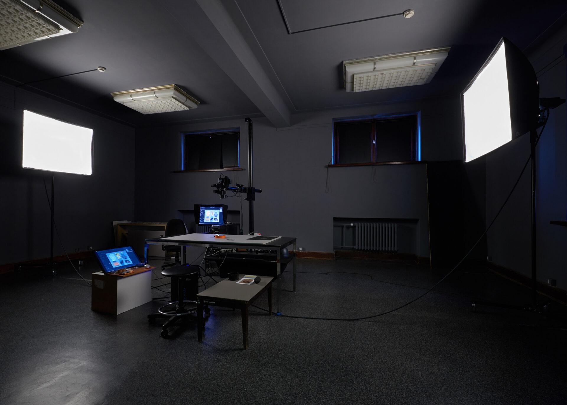 Fotografia pomieszczenia. przyciemniony pokój. Naśrodku biurka, monitory isprzęt dodigitalizacji.  Nadwóch przeciwległych ścianach pokoju jasne ekrany.