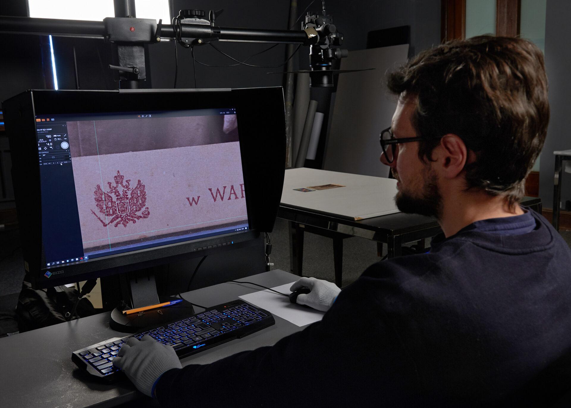 Fotografia. Pracownik digitalizacji pracuje przy komputerze.