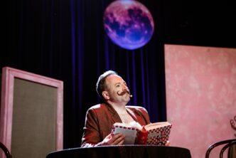 Fotografia. Aktor na scenia w teatrze trzymający książkę