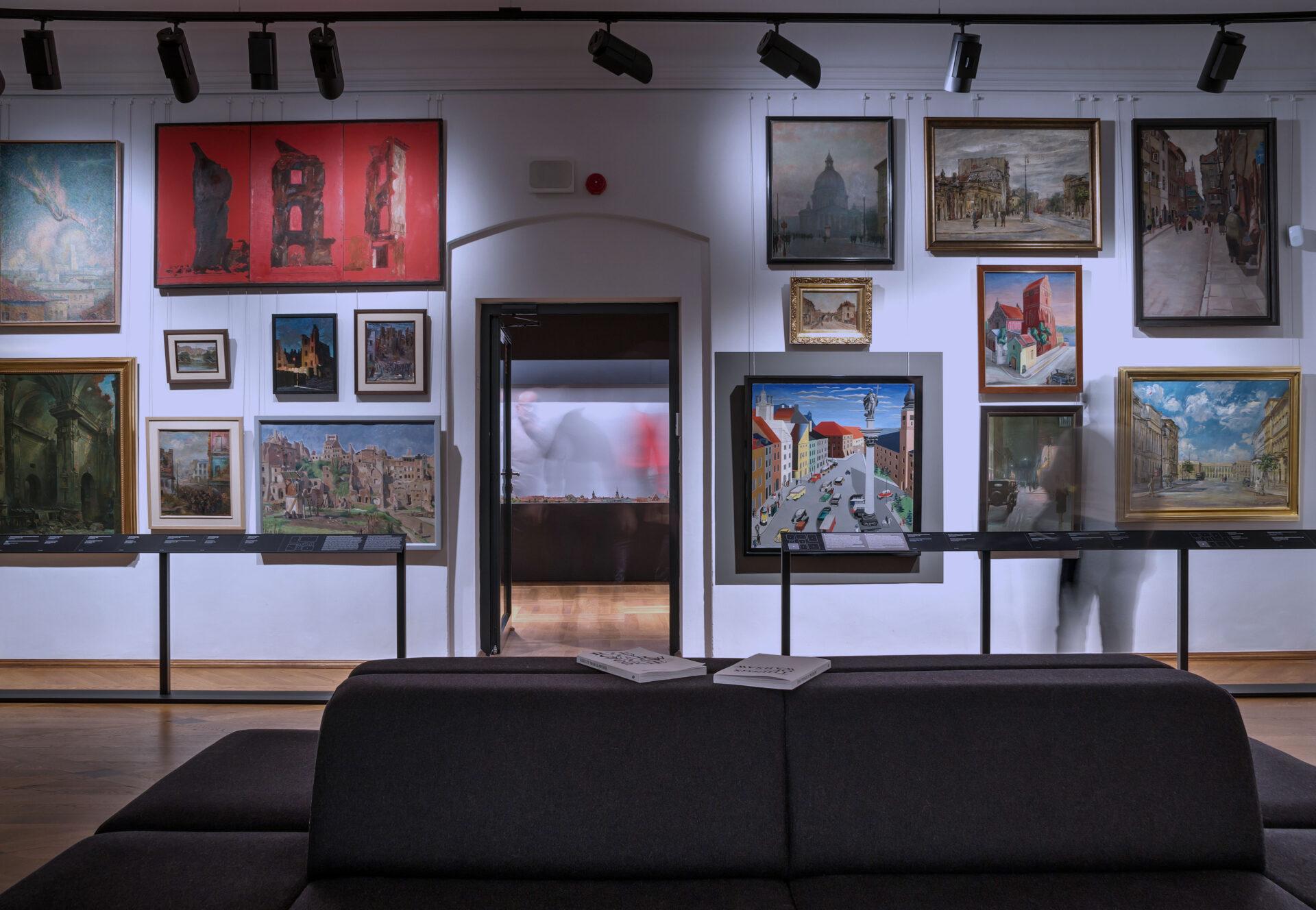 Zdjęcie gabinetu widoków Warszawy. Na ścianach kilka rzędów obrazów