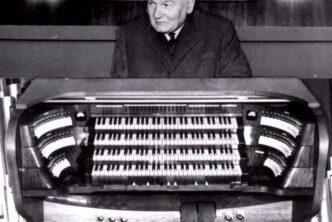 Czarno białe zdjęcie. Starszy mężczyzna siedzący za klawiaturą i na tle organów.